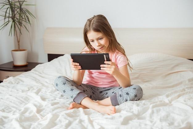 Chica adolescente feliz viendo la transmisión de películas en línea con tableta móvil digital y acostado en la cama en casa por la mañana, conexión de videollamada, distanciamiento social, concepto de tecnología de red