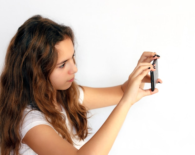 Chica adolescente graba video en un teléfono inteligente negro