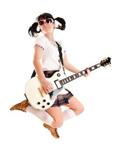 Chica adolescente con una guitarra eléctrica saltando