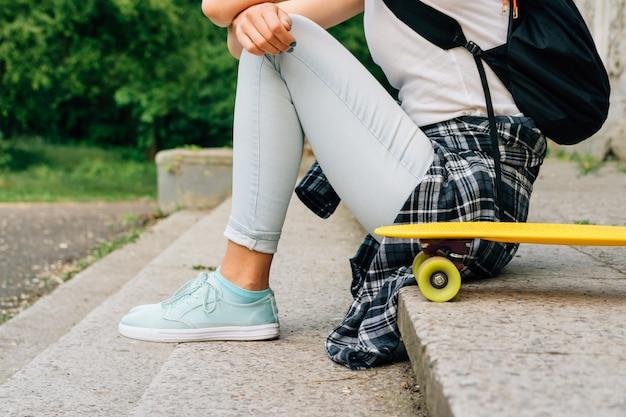 Chica adolescente en jeans y una camisa a cuadros sentados en los escalones cerca de su skate al aire libre
