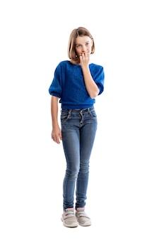 Una chica adolescente en jeans y una sudadera azul se muerde las uñas. altura completa. . vertical.