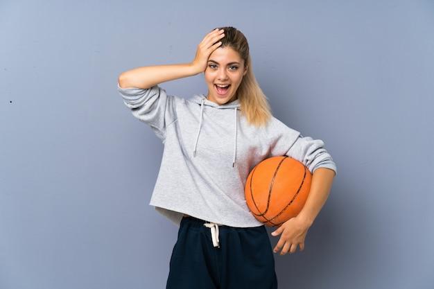 Chica adolescente jugando baloncesto sobre la pared gris con sorpresa y expresión facial conmocionada