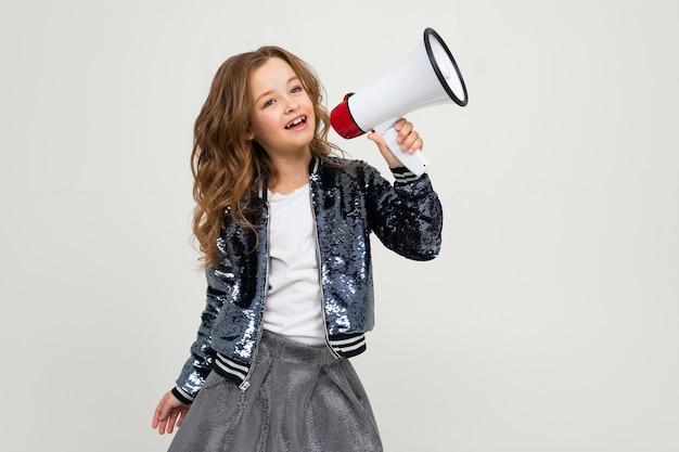 Chica adolescente linda europea con un megáfono informa la noticia con un megáfono en sus manos sobre un fondo blanco de estudio.