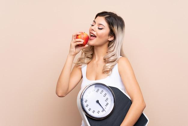 Chica adolescente con máquina de pesaje con máquina de pesaje y con una manzana