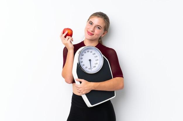 Chica adolescente con máquina de pesaje sobre blanco aislado con máquina de pesaje y con una manzana