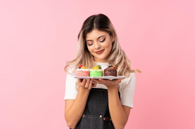 Chica adolescente con mini pasteles disfrutando el olor de ellos