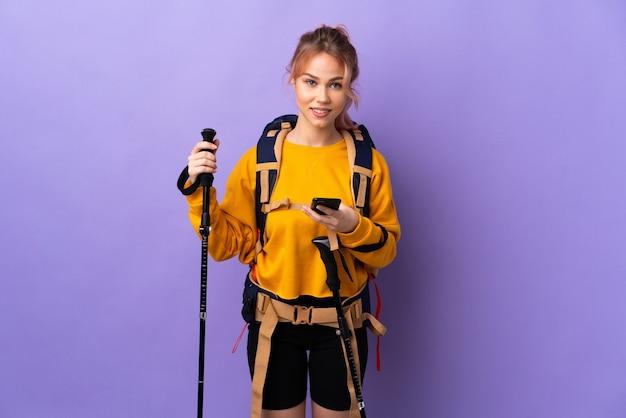 Chica adolescente con mochila y bastones de trekking sobre pared púrpura aislada enviando un mensaje con el móvil