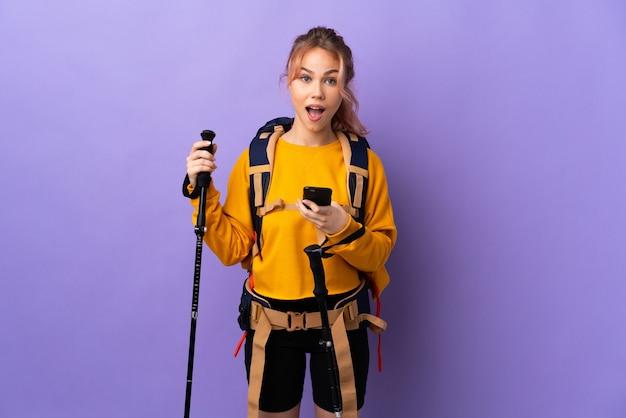 Chica adolescente con mochila y bastones de trekking sobre pared púrpura aislada sorprendida y enviando un mensaje