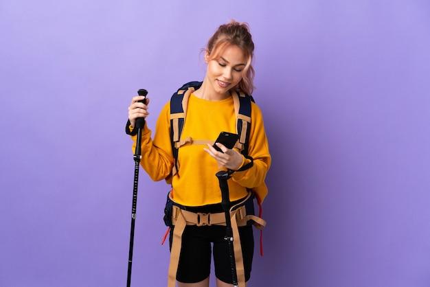 Chica adolescente con mochila y bastones de trekking sobre púrpura aislado enviando un mensaje con el móvil