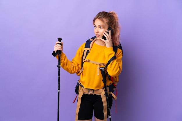 Chica adolescente con mochila y bastones de trekking sobre púrpura aislado manteniendo una conversación con el teléfono móvil con alguien