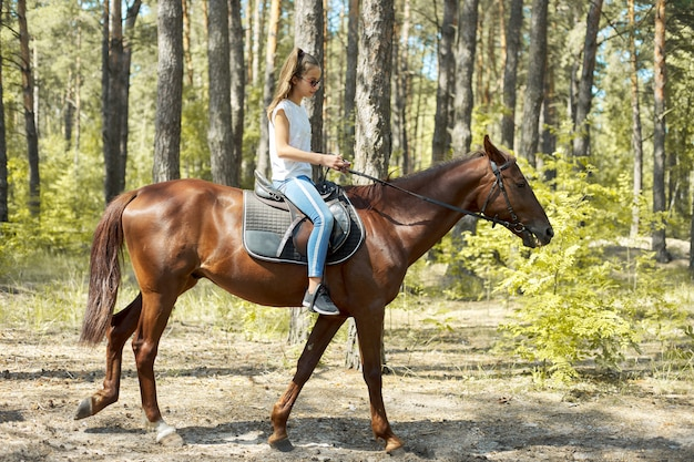 Chica adolescente montando un caballo marrón, paseos a caballo para personas en el parque