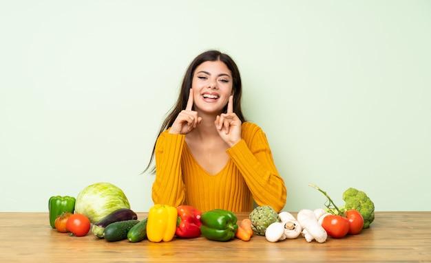 Chica adolescente con muchas verduras sonriendo con una expresión feliz y agradable