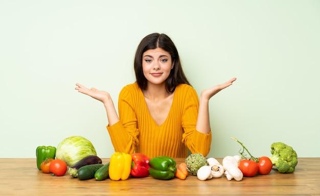 Chica adolescente con muchas verduras teniendo dudas mientras levanta las manos