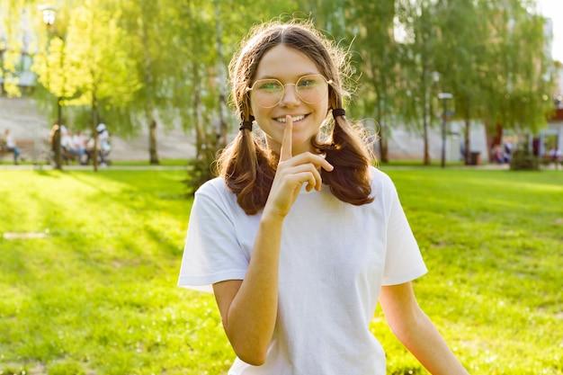 Chica adolescente muestra signo en silencio, secreto