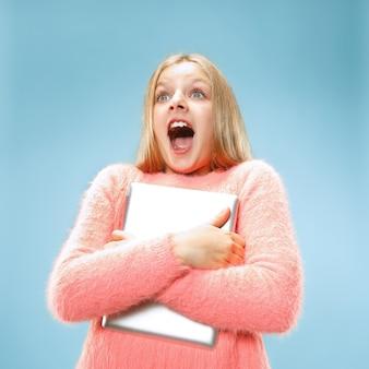 Chica adolescente con ordenador portátil. amor al concepto de computadora. retrato frontal de medio cuerpo femenino atractivo, fondo de color azul moderno del estudio. las emociones humanas, el concepto de expresión facial.