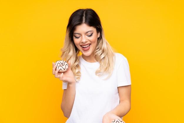 Chica adolescente en pared amarilla con donas con expresión feliz