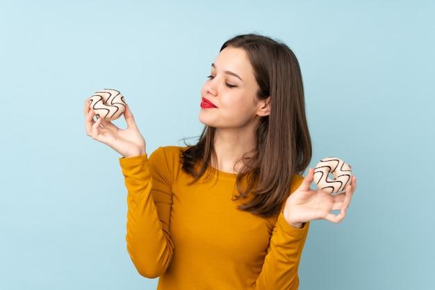 Chica adolescente en la pared azul con donas con expresión feliz
