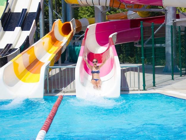 Chica adolescente en el parque acuático va desde el tobogán de agua hacia abajo.
