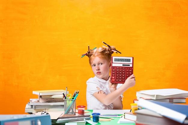 Chica adolescente pelirroja con muchos libros en casa. disparo