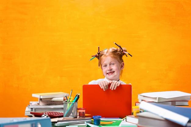 Chica adolescente pelirroja con muchos libros en casa.