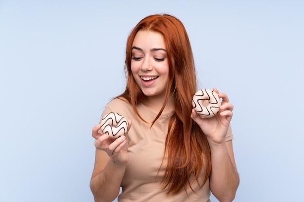 Chica adolescente pelirroja sobre pared azul aislada con donas con expresión feliz