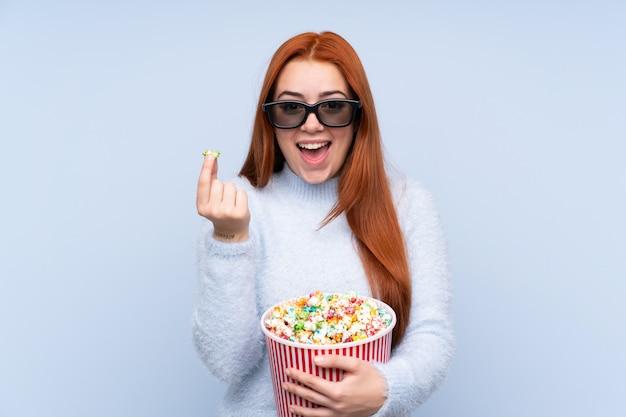 Chica adolescente pelirroja sobre pared azul aislada con gafas 3d y sosteniendo un gran cubo de palomitas de maíz