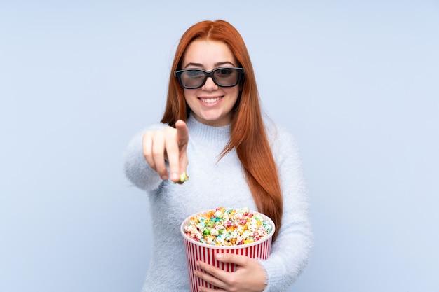 Chica adolescente pelirroja sobre pared azul aislada con gafas 3d y sosteniendo un gran cubo de palomitas mientras apunta hacia adelante