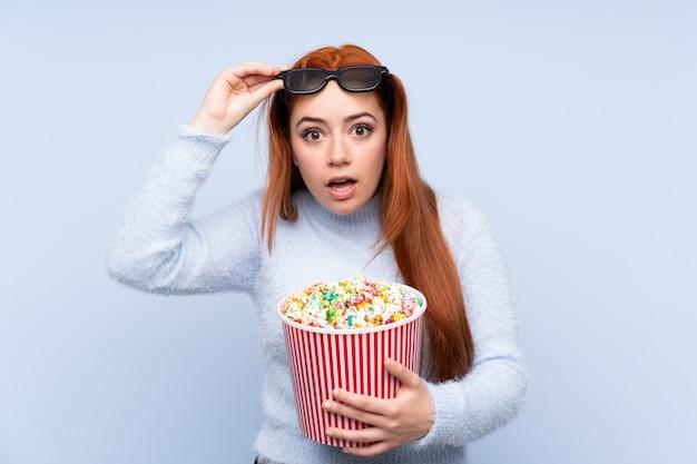 Chica adolescente pelirroja sobre pared azul aislada sorprendida con gafas 3d y sosteniendo un gran cubo de palomitas de maíz