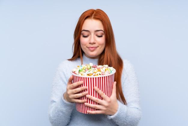 Chica adolescente pelirroja sobre pared azul aislado sosteniendo un gran cubo de palomitas de maíz