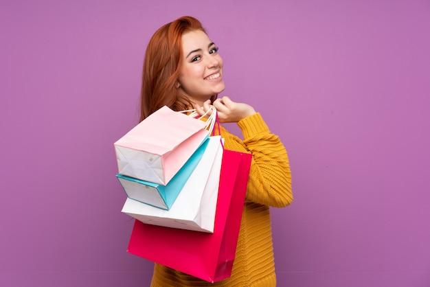 Chica adolescente pelirroja sobre púrpura sosteniendo bolsas de compras y sonriendo