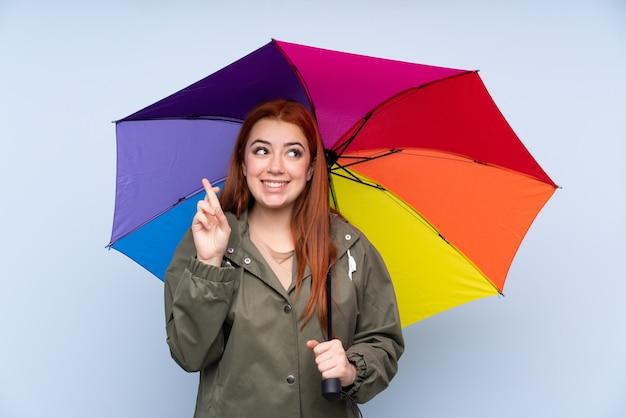 Chica adolescente pelirroja sosteniendo un paraguas sobre la pared azul aislada con cruzar los dedos