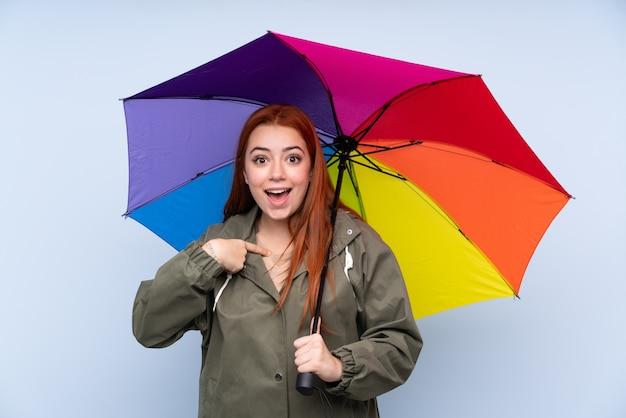 Chica adolescente pelirroja sosteniendo un paraguas sobre la pared azul aislada con expresión facial sorpresa