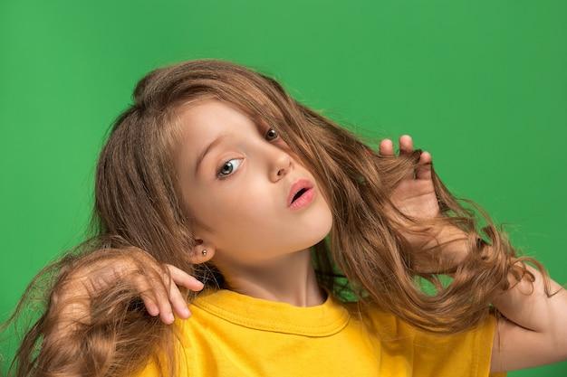 Chica adolescente pensativa de pie en el estudio verde