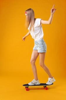 Chica adolescente de pie y posando en patineta sobre un fondo de color