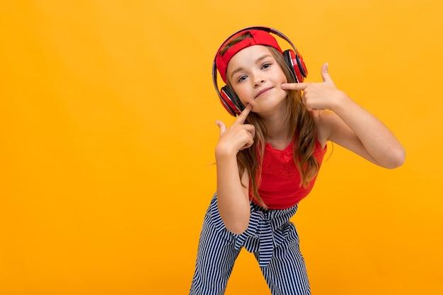 Chica adolescente rubia escucha música en auriculares grandes con una suscripción en un teléfono de lista de reproducción sobre un fondo amarillo.