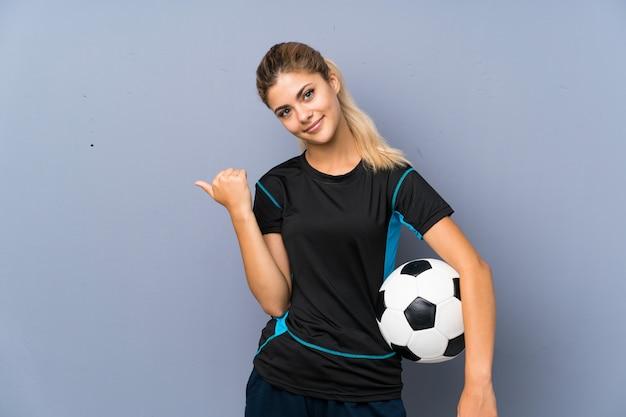 Chica adolescente rubia futbolista sobre pared gris apuntando hacia un lado para presentar un producto