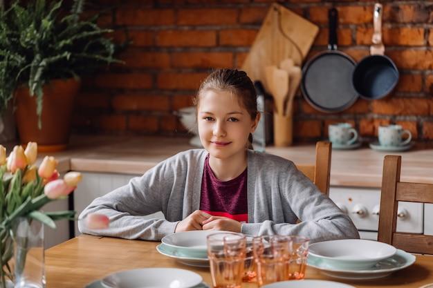 Chica adolescente sentado en la cocina. cocina tipo loft con paredes de ladrillo y nevera roja.