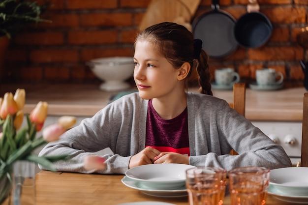 Chica adolescente sentado en la mesa de la cocina. cocina tipo loft con paredes de ladrillo y nevera roja.