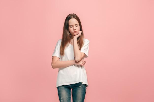 Chica adolescente seria, triste, dudosa y pensativa atanding en el estudio.