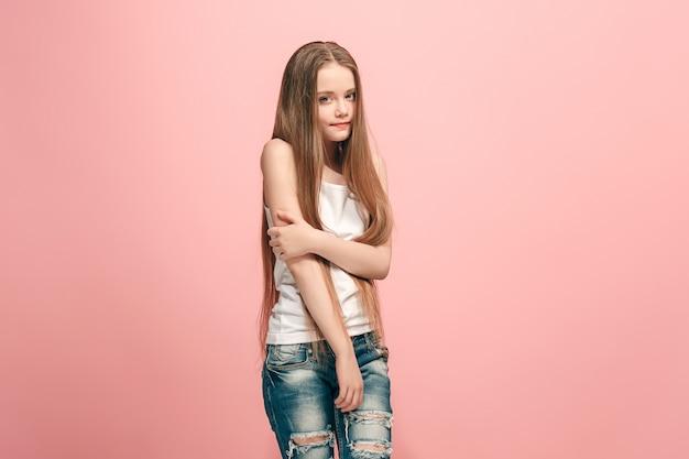 Chica adolescente seria, triste, dudosa, pensativa de pie en el estudio.
