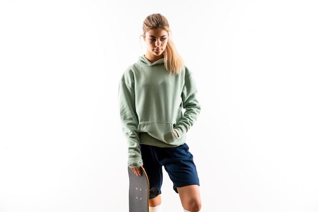 Chica adolescente skater rubia sobre fondo blanco aislado