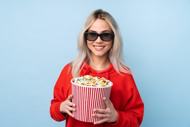 Chica adolescente sobre azul con gafas 3d y sosteniendo un gran cubo de palomitas de maíz