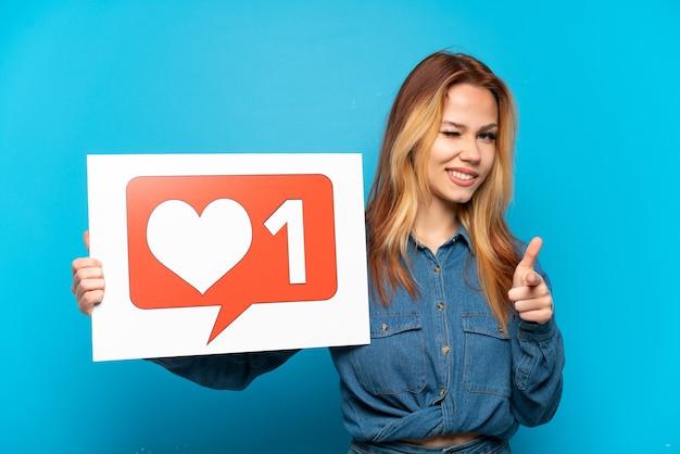 Chica adolescente sobre fondo azul aislado sosteniendo un cartel con el icono me gusta y apuntando hacia el frente