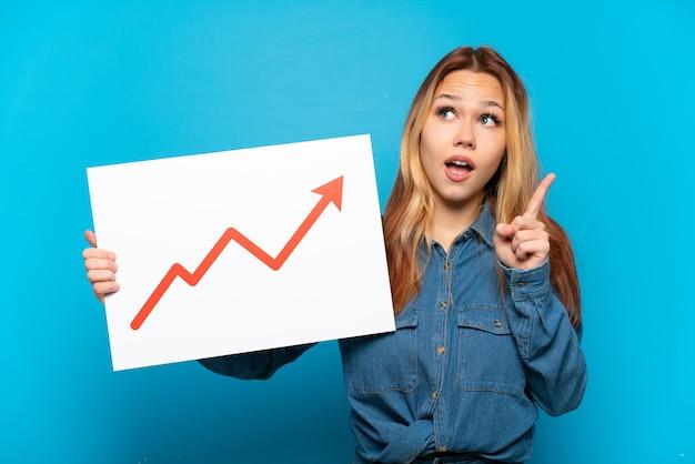 Chica adolescente sobre fondo azul aislado sosteniendo un cartel con un símbolo de flecha de estadísticas cada vez mayor y el pensamiento