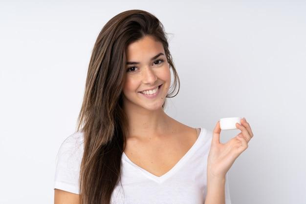 Chica adolescente sobre pared aislada con crema hidratante