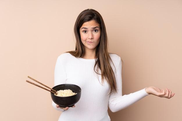 Chica adolescente sobre pared aislada haciendo gesto de dudas mientras levanta los hombros mientras sostiene un tazón de fideos con palillos
