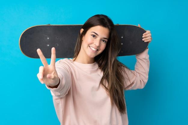 Chica adolescente sobre pared azul aislada con un patín haciendo gesto de victoria