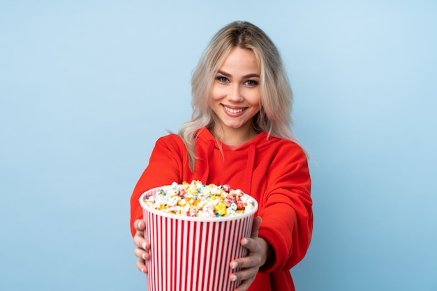 Chica adolescente sobre pared azul aislada sosteniendo un gran cubo de palomitas de maíz