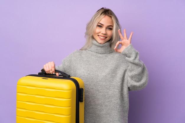 Chica adolescente sobre pared púrpura aislada en vacaciones con maleta de viaje y un sombrero