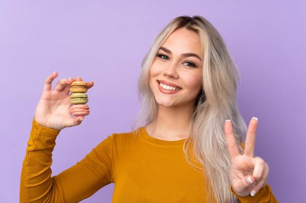 Chica adolescente sobre pared púrpura aislado sosteniendo coloridos macarons franceses y mostrando el signo de la victoria